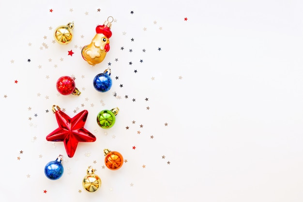 Weihnachtshintergrund mit dekorationen. glänzende bunte bälle, stern und konfetti. flachgelegt, draufsicht. platz für text.