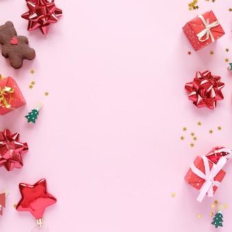 Weihnachtshintergrund mit dekorationen und geschenkboxen auf rosa