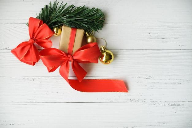 Weihnachtshintergrund mit dekorativer zusammensetzung des roten bogens und der goldenen weihnachtsbälle auf weißem hölzernem brett. frohes neues jahr.