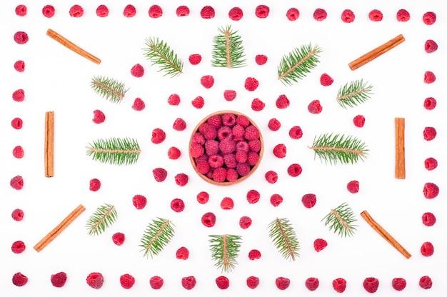 Weihnachtshintergrund mit den himbeeren und tannenzweigen getrennt auf weiß