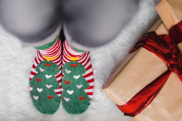 Weihnachtshintergrund mit der person, die wintersocken trägt