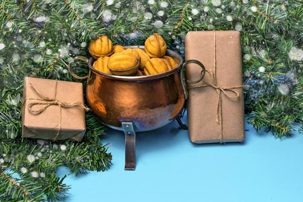 Weihnachtshintergrund mit einem weihnachtsbaum und einem behälter mit keksenüssen mit kondensmilch auf einem blauen hintergrund.