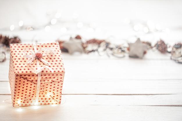 Weihnachtshintergrund mit einer geschenkbox und lichtkopienraum.