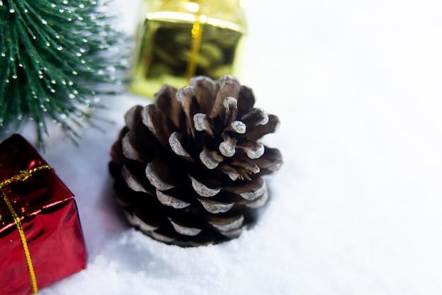 Weihnachtshintergrund mit einer roten kugel und, goldenes geschenk im schnee