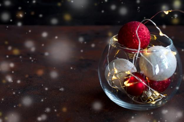 Weihnachtshintergrund mit festlicher dekoration, kerzen, licht und bällen im glas.