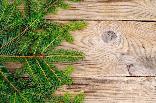Weihnachtshintergrund mit fichtenzweigen auf holzoberfläche