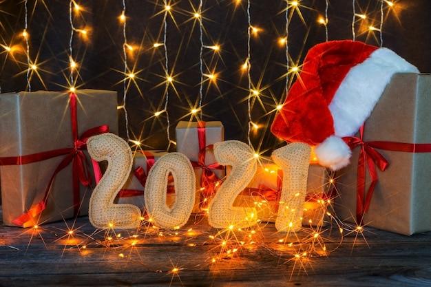 Weihnachtshintergrund mit gehäkeltem spielzeugbullen und zahlen 2021. hochwertiges foto