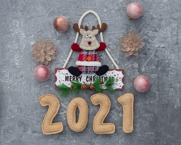 Weihnachtshintergrund mit gehäkelten zahlen 2021 und dekorativen verzierungen.