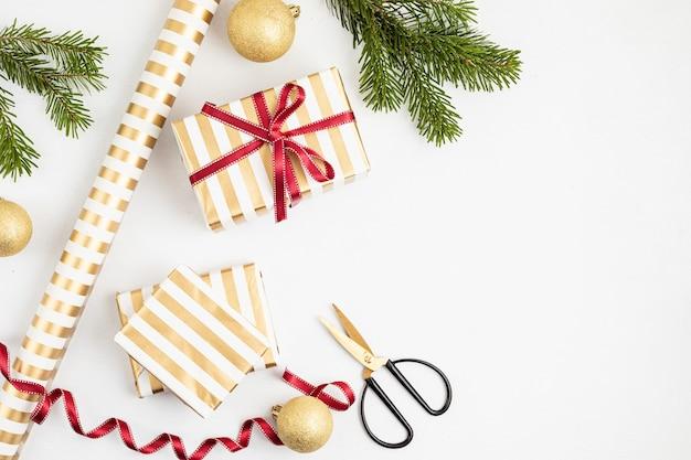 Weihnachtshintergrund mit geschenkboxen, band, papierrollen und weihnachtsverzierung