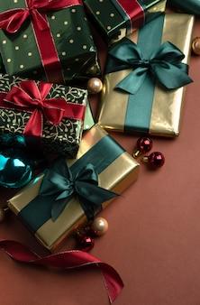 Weihnachtshintergrund mit geschenkboxen mit satinbändern auf rotem hintergrund