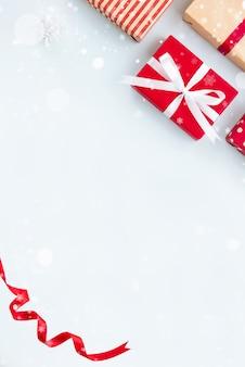 Weihnachtshintergrund mit geschenkboxen und gekräuseltem rotem band