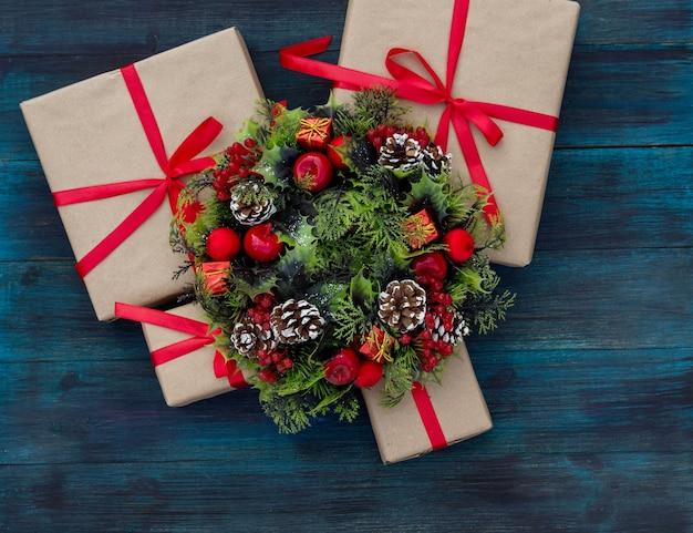 Weihnachtshintergrund mit geschenken gebunden mit einem roten band und einem dekorativen kranz