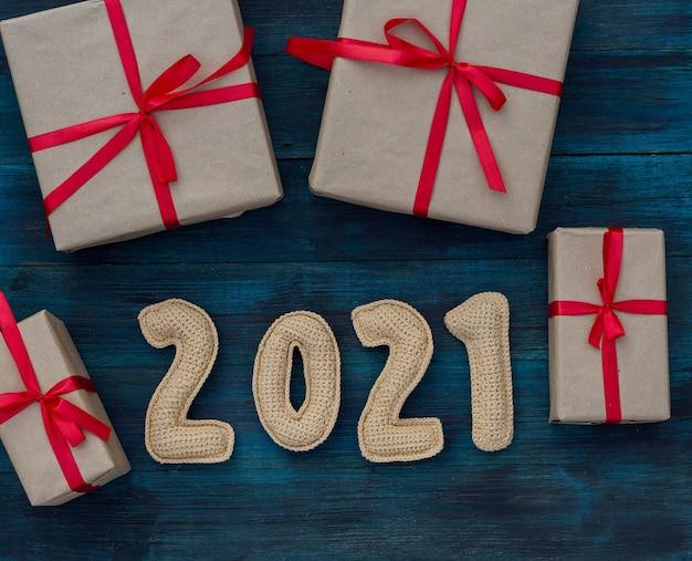 Weihnachtshintergrund mit geschrumpfter 2021 nummer und bastelpapier-geschenkboxen mit roten bändern