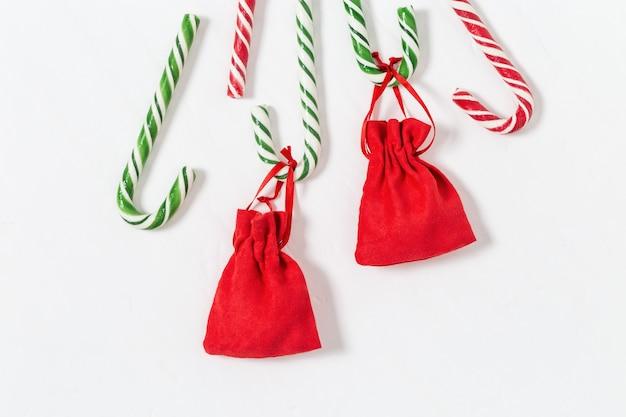 Weihnachtshintergrund mit gestreiften zuckerstangen und geschenken in der kleinen roten tasche. weihnachtszusammensetzung.