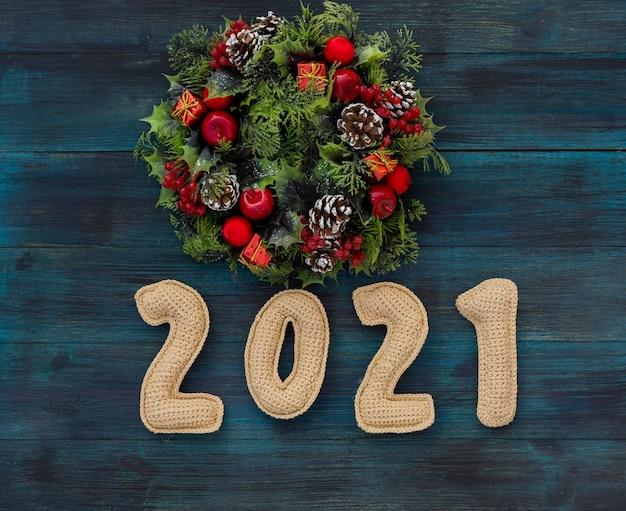 Weihnachtshintergrund mit gestrickten zahlen und dekorativem kranz
