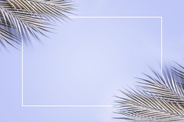 Weihnachtshintergrund mit glitzernden silbernen palmblättern auf blauem hintergrund mit weißem rahmen, kreativem winterweihnachts- oder neujahrslayout
