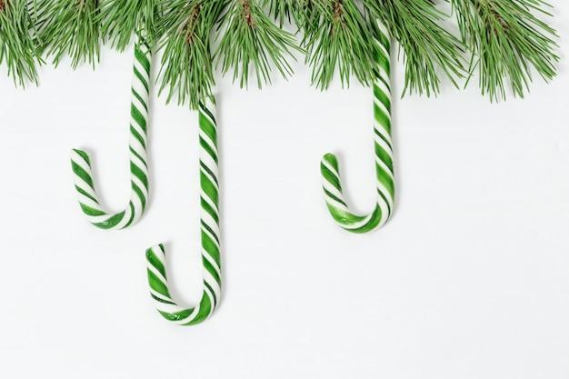 Weihnachtshintergrund mit grünen zuckerstangen und kiefer