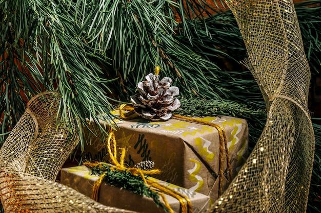 Weihnachtshintergrund mit handwerksgeschenkboxen goldene knäuel aus seil und dekorationen