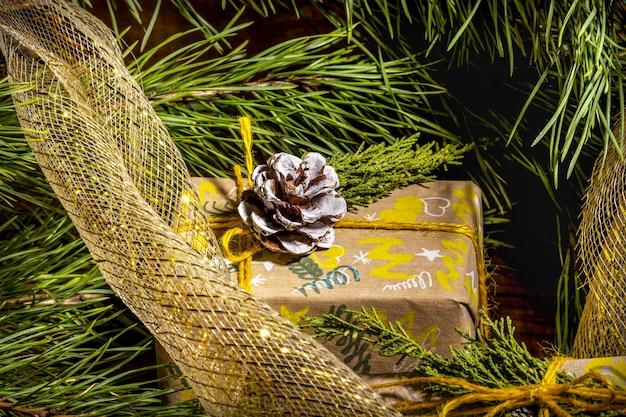 Weihnachtshintergrund mit handwerksgeschenkboxen goldene seilknäuel und dekorationen mit kiefer