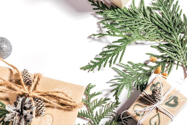 Weihnachtshintergrund mit handwerksgeschenkboxen knäuel aus seil und dekorationen mit kiefernzapfen