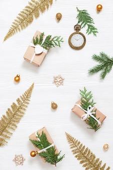 Weihnachtshintergrund mit hellem goldenem spielzeug handwerksgeschenk mit natürlichen grünen thujazweigen