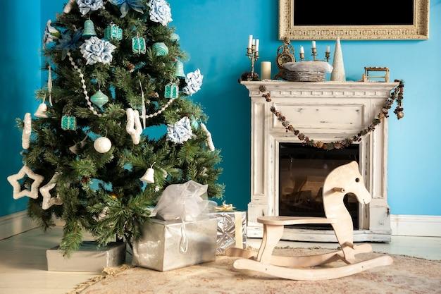 Weihnachtshintergrund mit kamin und schaukelpferdestuhlspielzeug