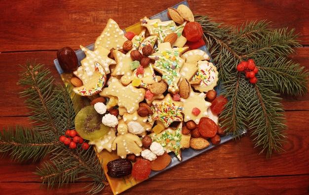 Weihnachtshintergrund mit lebkuchenplätzchen mit nüssen und früchten