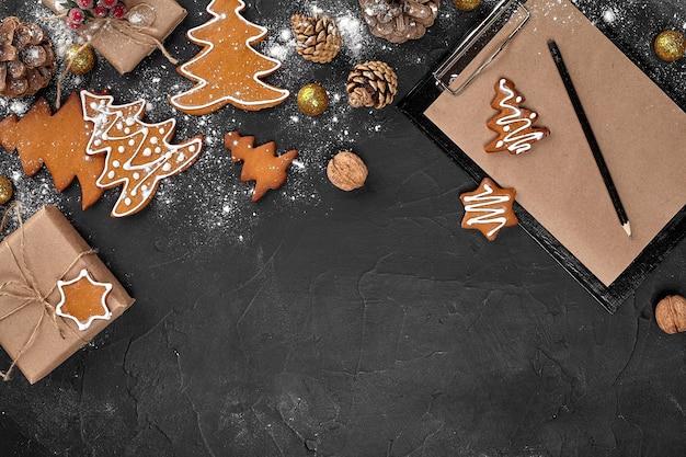 Weihnachtshintergrund mit lebkuchenplätzchen und bastelpapier. platz kopieren. ansicht von oben