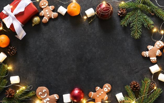 Weihnachtshintergrund mit lebkuchenplätzchen und geschenken. neujahrslayout auf schwarzem hintergrund.