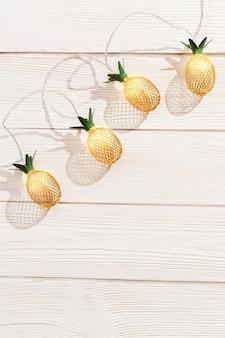 Weihnachtshintergrund mit lichterketten als goldene ananas auf weißem holz
