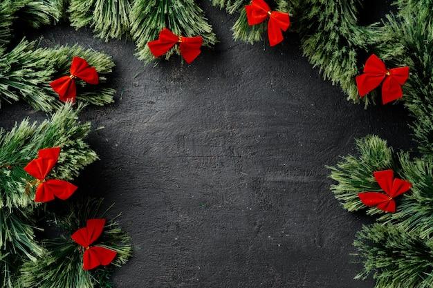 Weihnachtshintergrund mit passenden ästen und roten bändern auf schwarz mit kopienraum