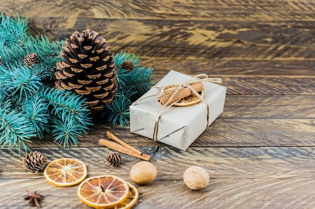 Weihnachtshintergrund mit platz für ihren text. ein großer kegel aus zedernholz, zweige aus blaufichte, eine schachtel mit einem geschenk und natürlichen organischen materialien.
