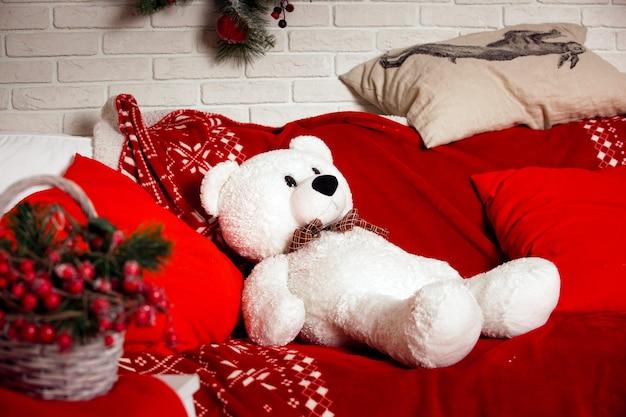 Weihnachtshintergrund mit rotem sofa und weißem bärenspielzeug sitzend