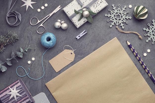 Weihnachtshintergrund mit roten steinherzen, eingewickelten geschenken, tags, schnüren und schmuckstücken auf dunkelheit, kopieraum