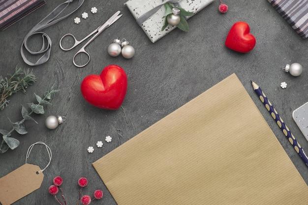 Weihnachtshintergrund mit roten steinherzen, verpackten geschenken, tags, schnüren und schmuckstücken auf dunklem, kopierraum.