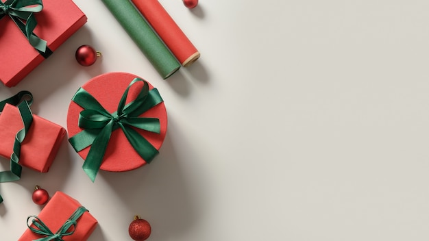 Weihnachtshintergrund mit roten und grünen geschenkboxen, papierrollen auf grau. frauenvorbereitungs- und verpackungsgeschenk für feiertage. draufsicht mit kopierraum.