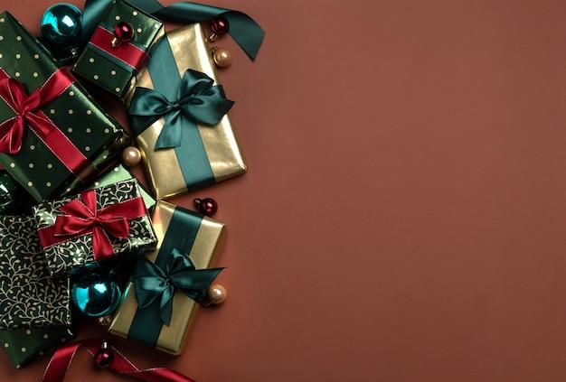 Weihnachtshintergrund mit satinbändern der geschenkboxen auf braunem hintergrund