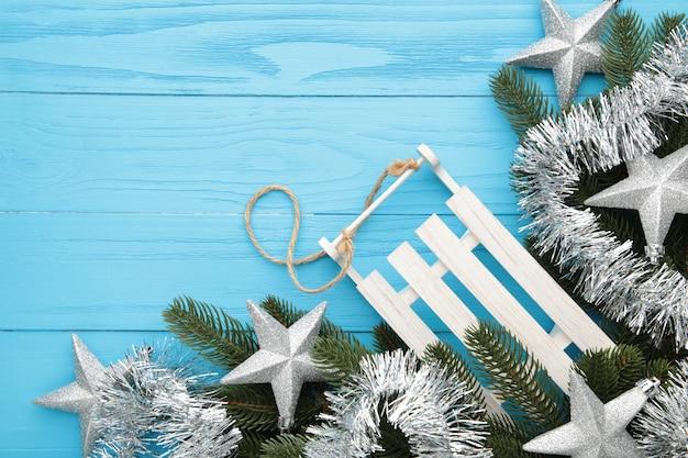 Weihnachtshintergrund mit schlitten und dekorationen auf blauem hölzernem hintergrund. draufsicht.