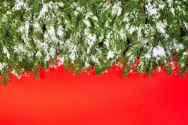 Weihnachtshintergrund mit schnee lokalisiert auf einem roten hintergrund
