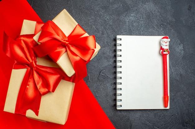 Weihnachtshintergrund mit schönen geschenken mit bogenförmigem band auf einem roten handtuch und notizbuch mit stift auf einem dunklen hintergrund