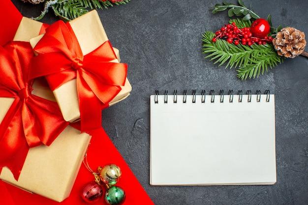 Weihnachtshintergrund mit schönen geschenken mit bogenförmigem band und notebook-tannenzweig-dekorationszubehör auf einem dunklen tisch