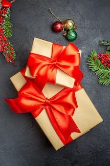 Weihnachtshintergrund mit schönen geschenken mit bogenförmigem band und tannenzweigdekorationszubehör auf einem dunklen tisch über ansicht