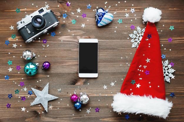 Weihnachtshintergrund mit smartphone, altmodische kamera, roter sankt hut, dekorationen