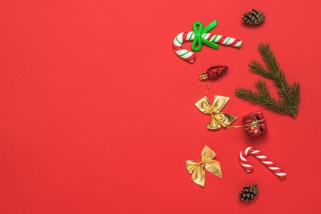 Weihnachtshintergrund mit süßigkeiten, fichtenzweigen und goldenen schleifen.