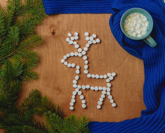 Weihnachtshintergrund mit tanne, rotwild, schal, tasse kaffee