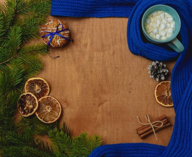 Weihnachtshintergrund mit tanne, schal, trockener orange, kegel, kekse, zimt