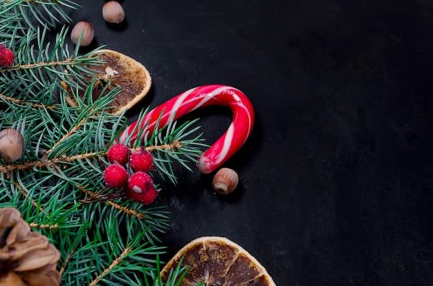Weihnachtshintergrund mit tanne, trockene kandierte früchte, süßigkeitsstöcke