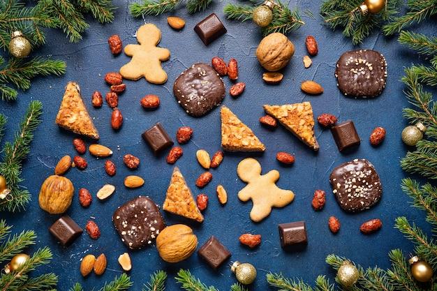 Weihnachtshintergrund mit tannenbaum und süßigkeiten auf dunkelblauer oberfläche