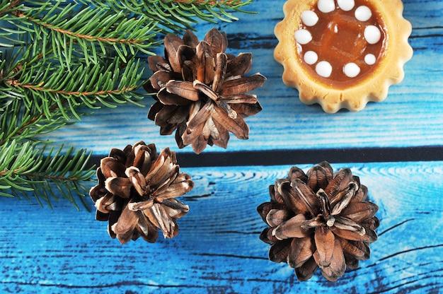 Weihnachtshintergrund mit tannenzapfen, baumasten und kuchen