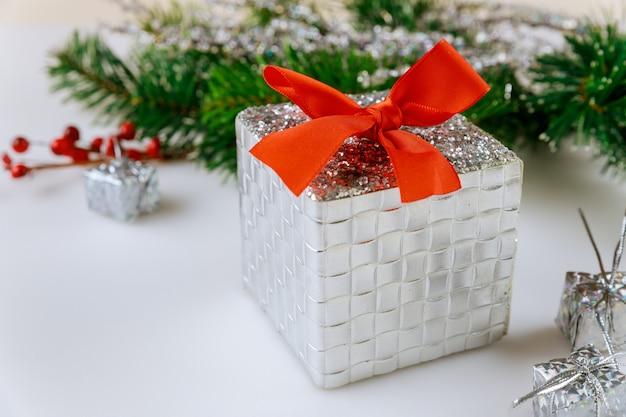 Weihnachtshintergrund mit tannenzweig, roten beeren und geschenk auf weißem hintergrund.